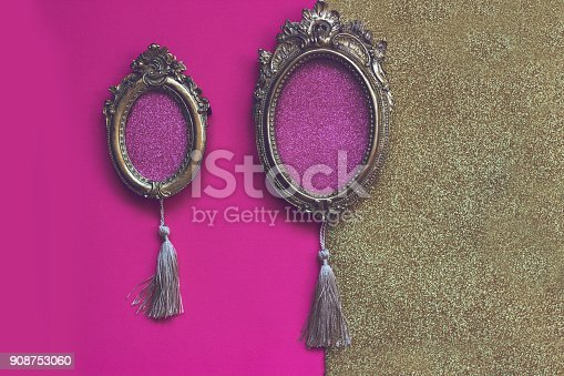 istock Two vintage golden oval picture frames on pink and golden background, with copy space in the frame 908753060