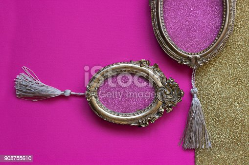 istock Two vintage golden oval picture frames on pink and golden background, with copy space in the frame 908755610