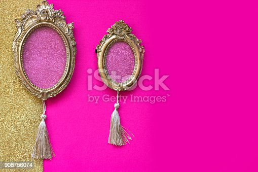 istock Two vintage golden oval picture frames on pink and golden background, with copy space in the frame 908756074