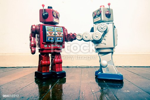 two vintage robot shake hands on a old wooden floor  toned image