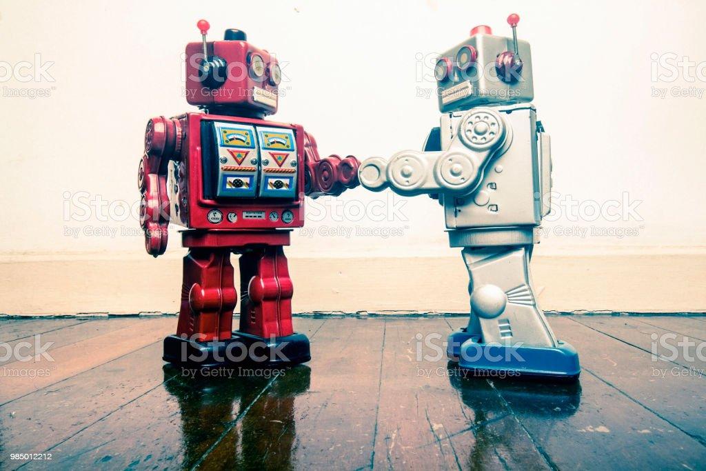 robô vintage dois apertar as mãos sobre um piso de madeira antigo - foto de acervo