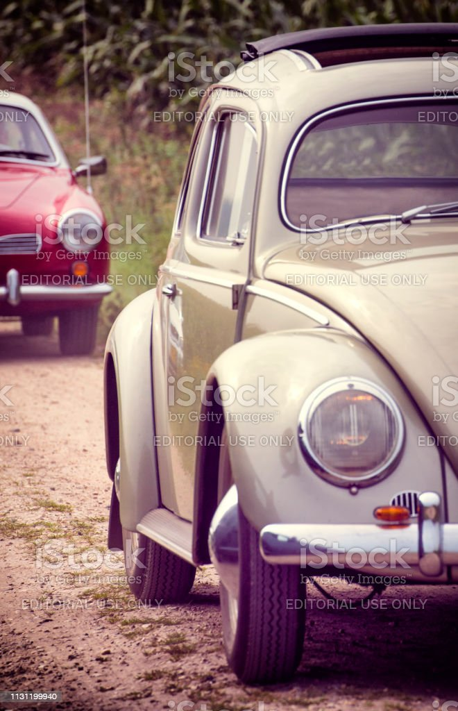Two vintage Volkswagen cars, a Beetle and Karmann Ghia driving on a country road stock photo