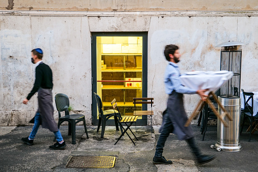 Rome, Italy, October 28 -- Two waiters withdraw tables and chairs as they close their restaurant in the Ghetto due the lockdown against the Covid-19 epidemic. The popular Jewish quarter of Rome occupies an ancient area of the city between the Capitoline Hill and the River Tiber. Image in High Definition format.