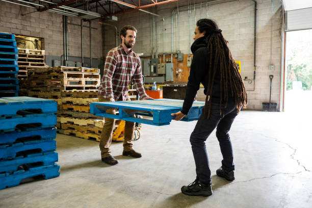 Two warehouse workers correctly using a two person lift to move a pallet. stock photo