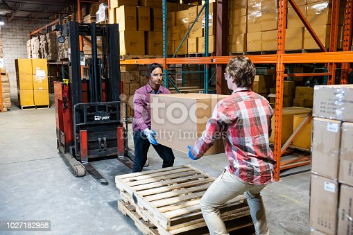 A warehouse worker calls his coworker over to help lift a heavy box.  Two person lifts, also known as buddy lifts is standard back safety practice for manual workers.