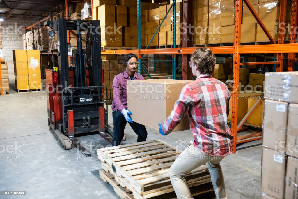 Two warehouse workers preparing to lift a heavy box together stock photo