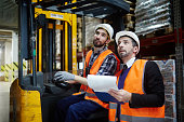 Portrait of warehouse manager and loader riding forklift truck inventorying stock