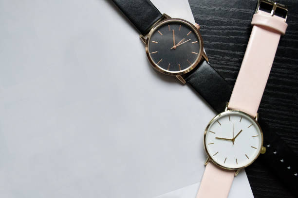 Two watches black and pink color, without numbers on a black table. Light paper, place for your text. Fashionable concept, top view stock photo