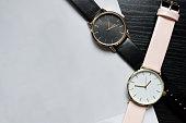 黒いテーブルの上の番号なしの黒とピンクの色の 2 つの時計します。紙の光、あなたのテキストの配置。ファッショナブルな概念、トップ ビュー