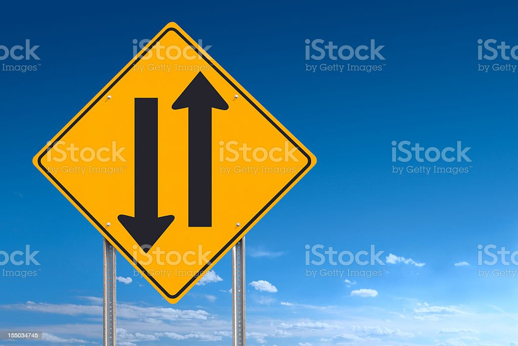 Two Way Road Sign Showing Opposing Directions on Blue Sky stock photo