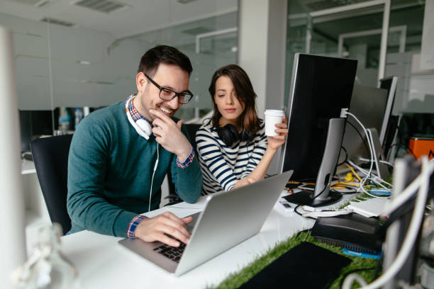 Two web designers working in office on a project together stock photo
