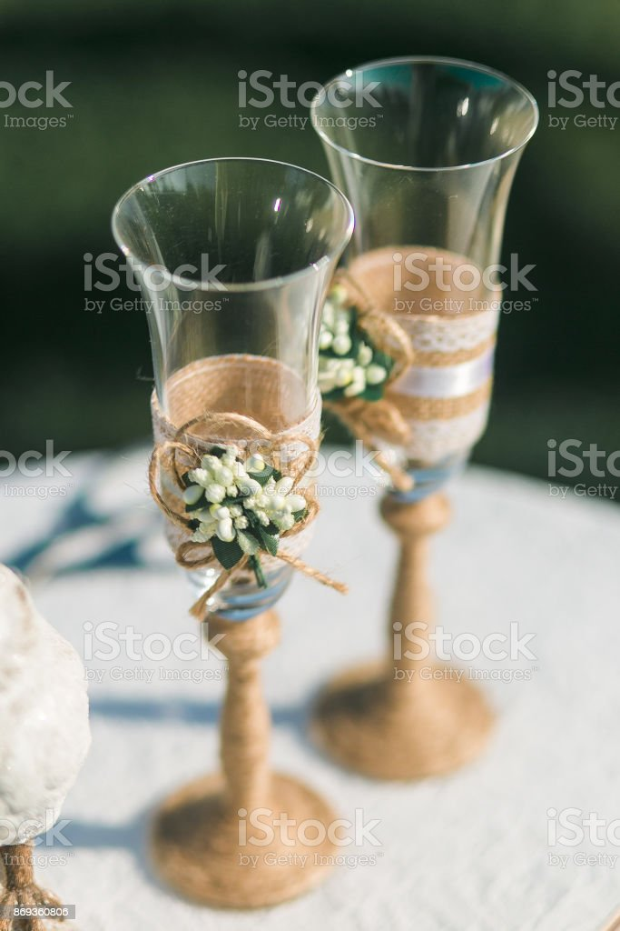 Two wedding champagne glasses decorated with twine and flowers standing on table stock photo