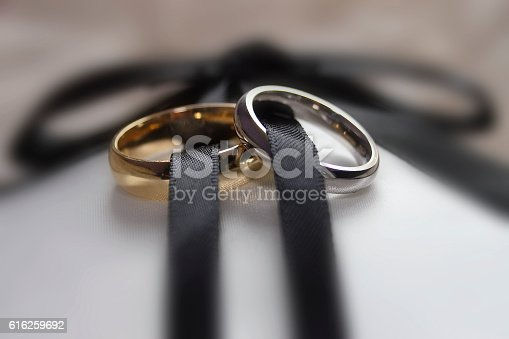 istock Two wedding rings male and female linked by ribbon 616259692