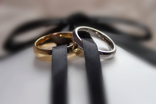 Two wedding rings male and female linked by ribbon