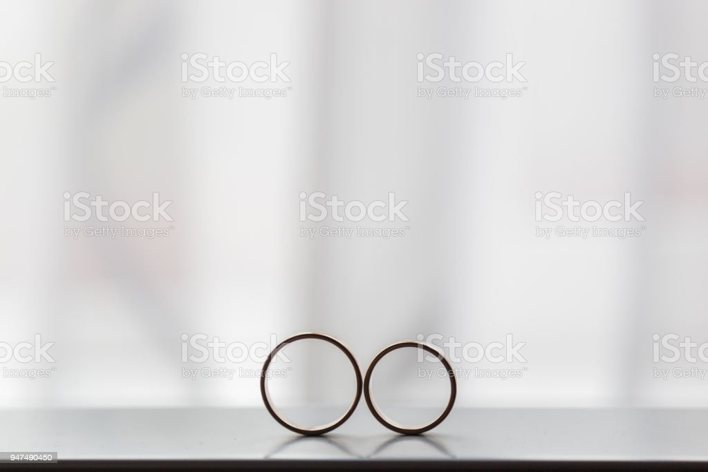 Two wedding rings next to the window stock photo