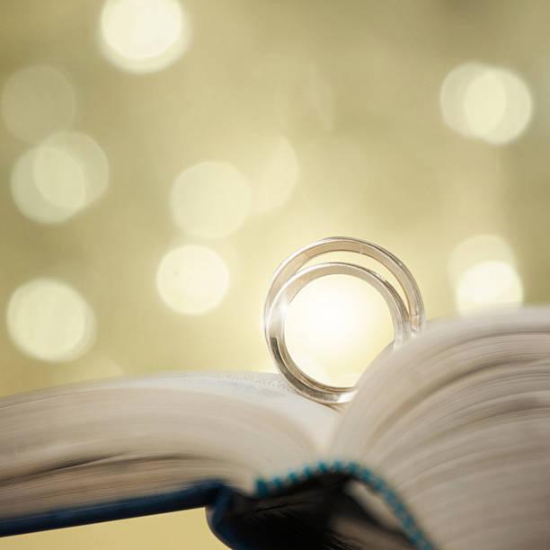 zwei hochzeit ringe auf eine bibel seite - verse zur hochzeit stock-fotos und bilder
