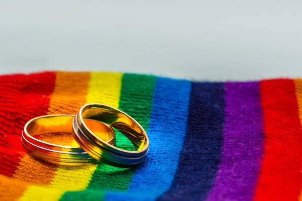 Two wedding rings on the fabric colors of the rainbow. Concept same-sex marriage. Two wedding rings on the fabric colors of the rainbow. Concept same-sex marriage. battle of the sexes concept stock pictures, royalty-free photos & images
