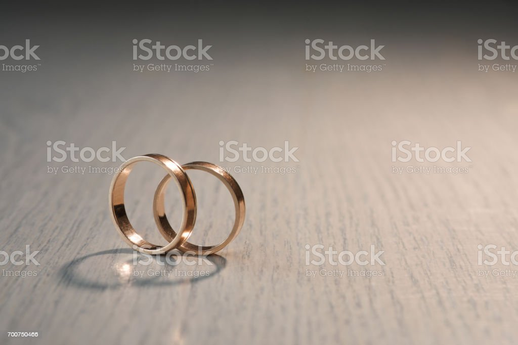 Two wedding rings on wood background stock photo