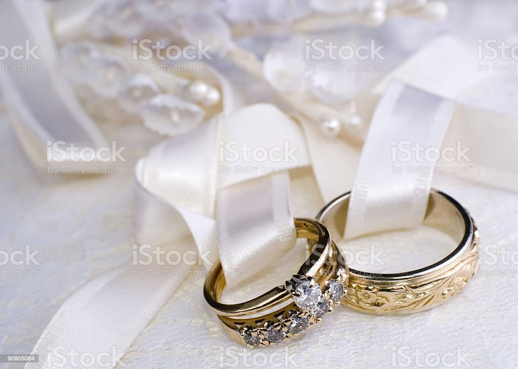 Two wedding rings tied to a pillow stock photo