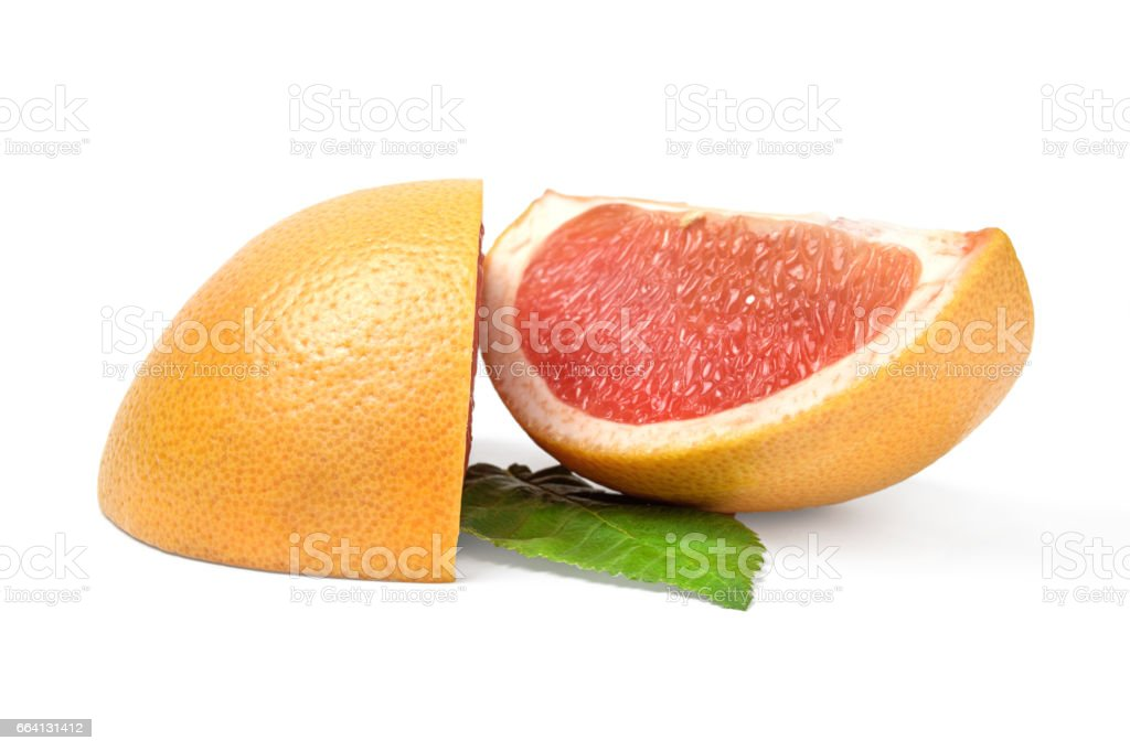 Two wedges of grapefruit on white background with green leaf foto stock royalty-free