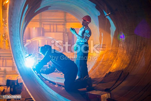 Two welders work in a pipe for an oil pipeline.