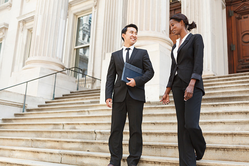 A well dressed man and woman smiling as they as they walk down steps of a courthouse  building. Could be business or legal professionals.