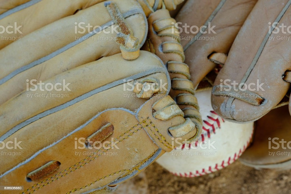 Two well used and vintage baseball gloves with a baseball sit in the...