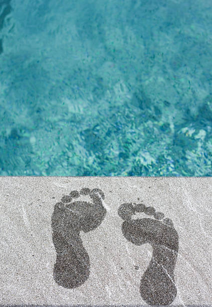 Two wet foot steps by swimming pool stock photo