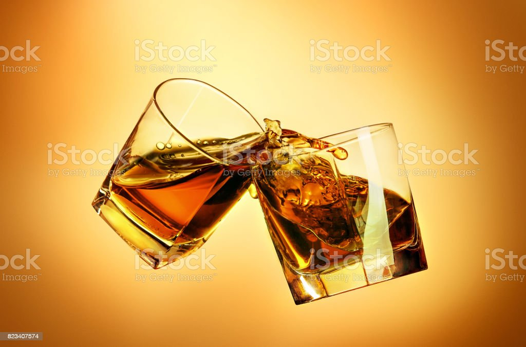 Two whiskey glasses clinking together on brown stock photo