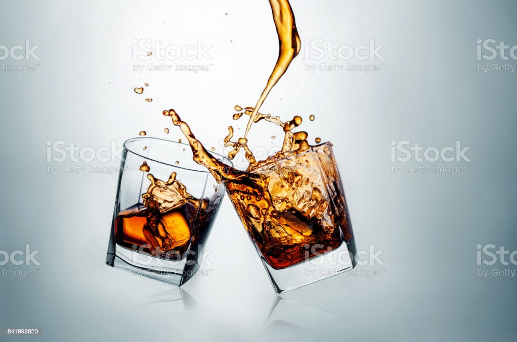 Two whiskey glasses clinking together on gray stock photo