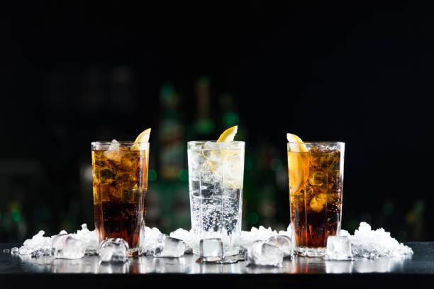 zwei whisky und cola, cocktails und einem weißen alkoholischen drink an der bar tisch. - alkoholfreies getränk stock-fotos und bilder