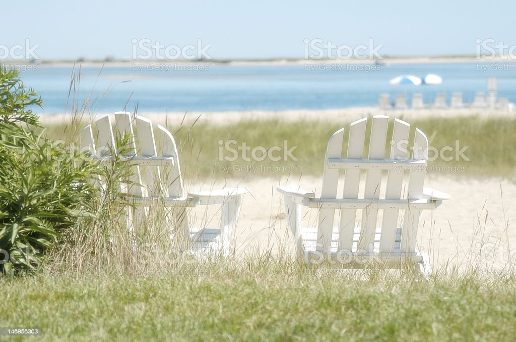 Two white Adirondack chairs near the shore stock photo