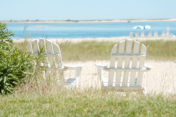 Two white Adirondack chairs near the shore white adirondack chairs, cape cod, beach, ocean, natural beach cape cod stock pictures, royalty-free photos & images