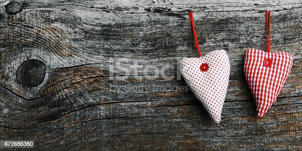 Two white and red material hearts on a dark wooden background in 18: 9 format