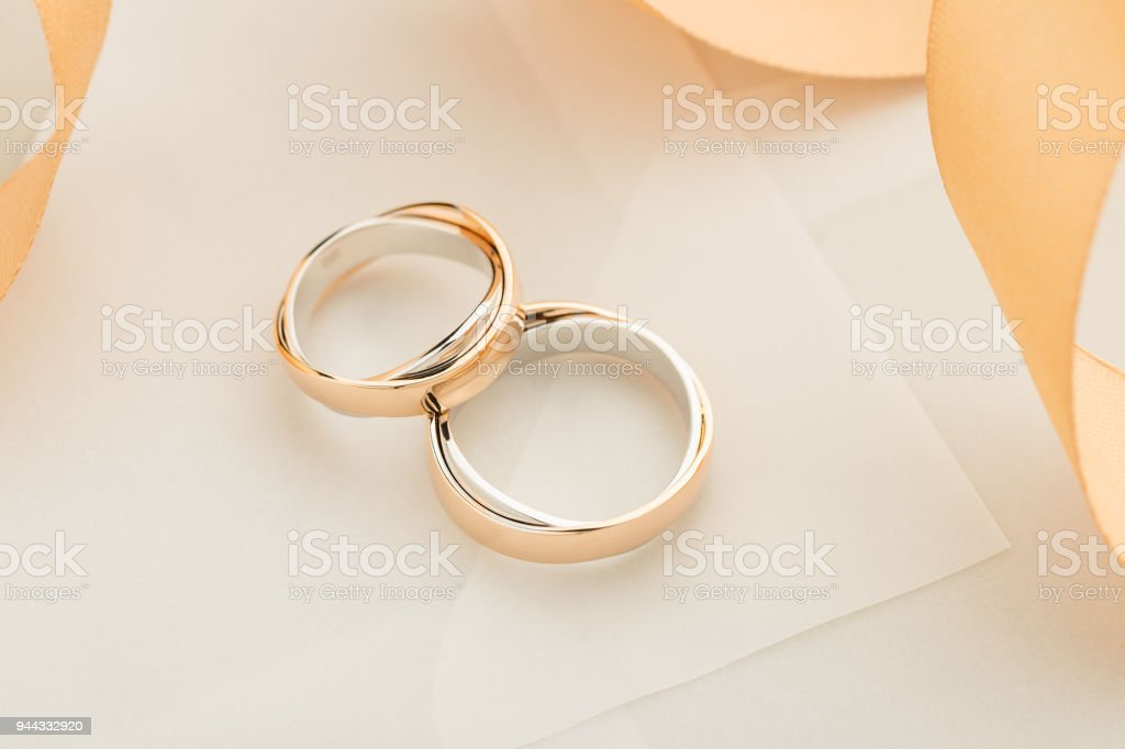 Two white and rose gold wedding rings on pastel background with...