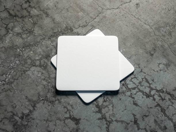 zwei weiße bierdeckel mock-up auf dem betonboden - untersetzer stock-fotos und bilder