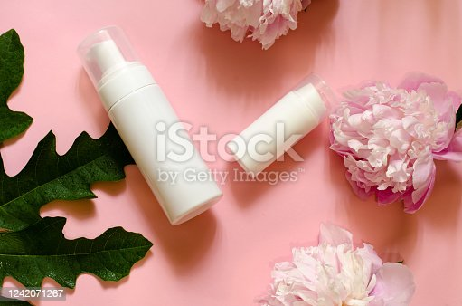 1128479585 istock photo Two white bottles of different sizes on a pink background with flowers and leaves. Beauty concept. 1242071267