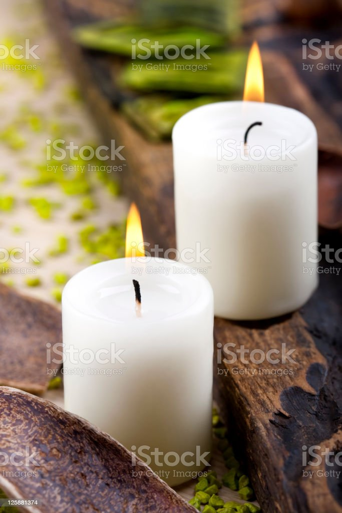 Two white candles and wooden parts arrangement stock photo
