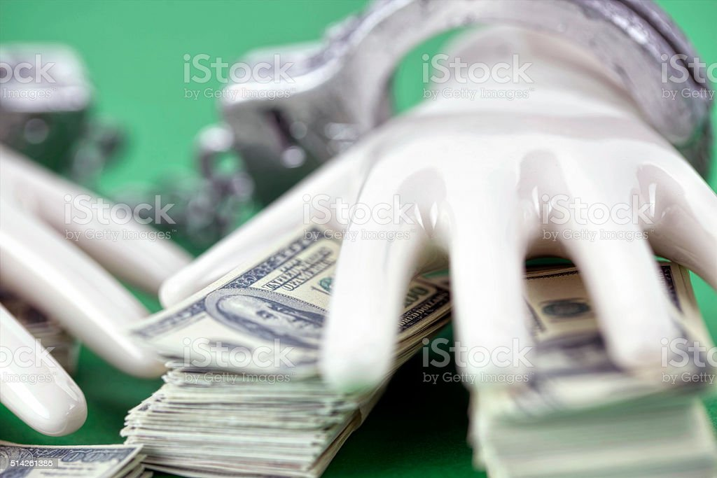 two white ceramic  hands with handcuffs on pile of 100 stock photo