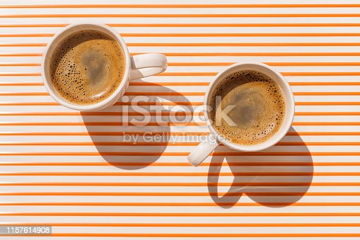 Two white coffee cup on orange striped table at direct sunlight. Top view with shadow