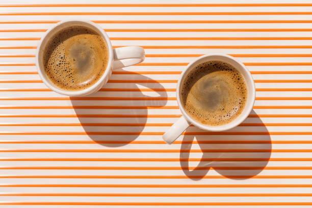 zwei weiße kaffeetasse auf orange gestreifte tischplatte ansicht - espresso stock-fotos und bilder