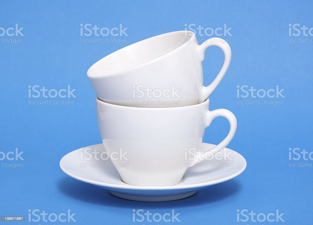 Two white coffee cup piled on blue background royalty-free stock photo