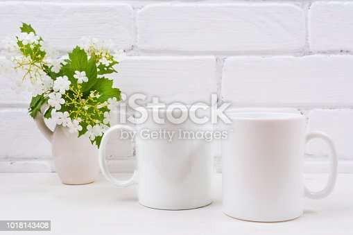 Two white coffee mug mockup with flowering viburnum branch.  Empty mug mock up with flowers for design promotion.