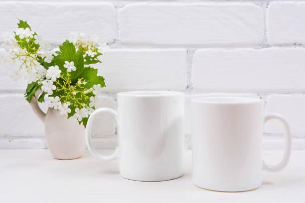 Two white coffee mug mockup with viburnum flowers stock photo