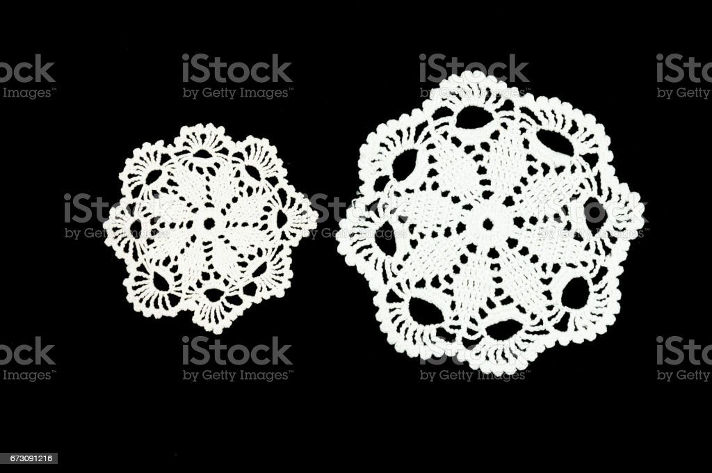 Two white crocheted coasters on the black background. Lace doily. stock photo