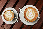 Two white cups of cappuccino with latte art