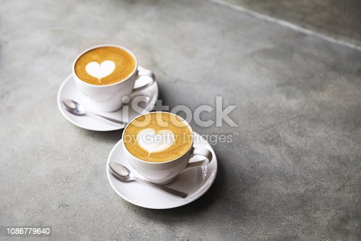 istock Two white cups of tasty cappucino with love art latte. Valentine's concept. 1086779640