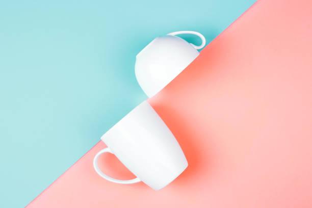 deux tasses blanches sur fond de couleur. - tasse flat photos et images de collection