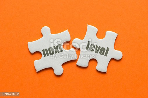 istock Two white details of puzzle with text Next Level on orange background, close up. 978477012