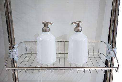 istock Two white dispenser bottles on metal bathroom shelf. 1137852648